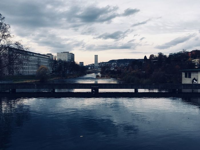 River by cityscape against sky
