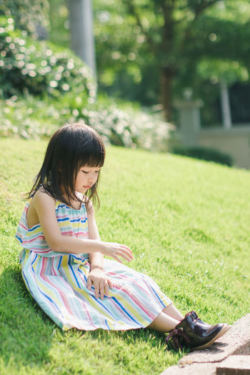 Bangs Casual Clothing Child Childhood Cute Day Females Field Full Length Girls Grass Hairstyle Innocence Leisure Activity One Person Outdoors Plant Real People Sitting Women