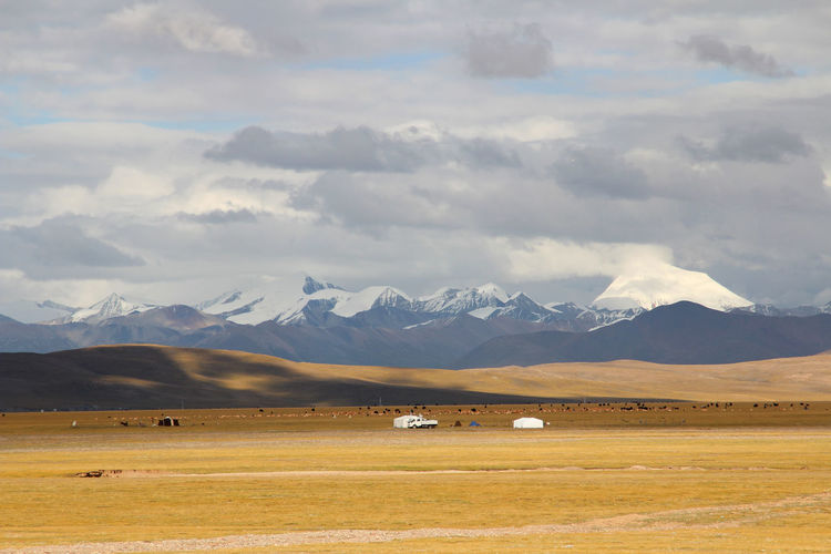 View of Tanggula Mountains, grassland, Nomadic tents with the dramatic sky near Namtso in Tibet, China Beauty In Nature Cloud - Sky Day Landscape Mountain Mountain Peak Mountain Range Namtsolake Nature No People Outdoors Scenics Sky Tanggula Mountains