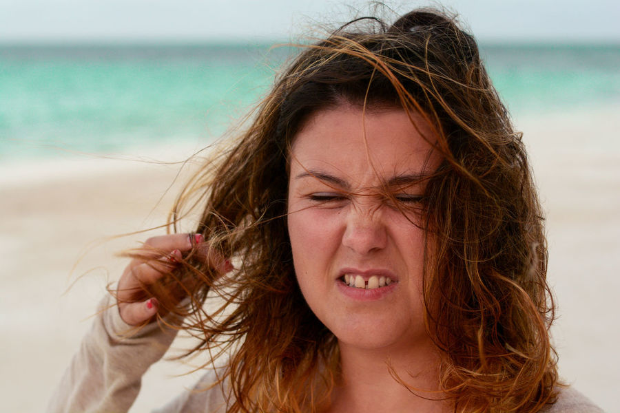 Adult Adults Only Anger Beach Beautiful Woman Brown Hair Close-up Day Eyes Closed  Front View Headshot Horizon Over Water Human Body Part Nature One Person Outdoors People Portrait Real People Sand Sea Tangled Hair Water Young Adult Young Women