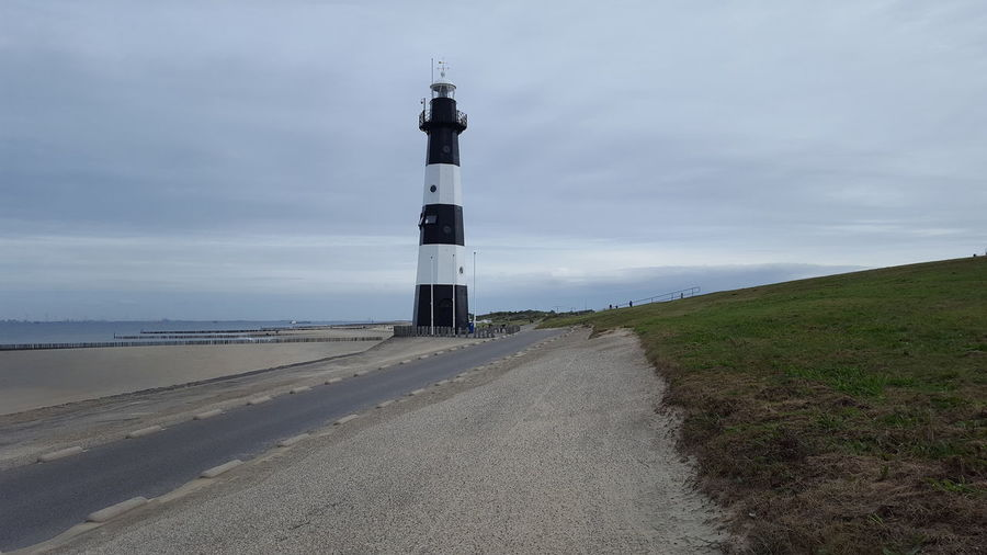 Lighthouse amidst road and buildings against sky