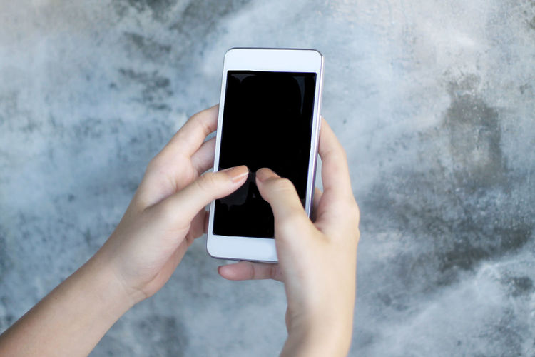 Cropped hands of woman using smart phone by wall