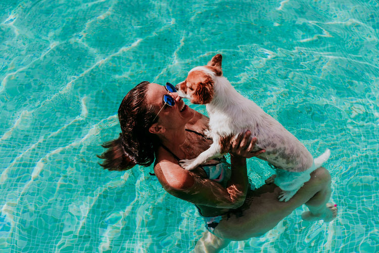 High angle view of woman with dog swimming in pool