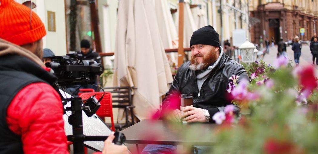 Smiling man with coffee sitting at sidewalk