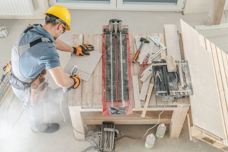 Caucasian Construction Worker and His Workplace. Men Cutting Ceramic Tiles. Makeover Construction Remodeling Job Worker Hard Hat Equipment Workplace Apartment Building Ceramic Tiles Cutting Power Tool Caucasian Men