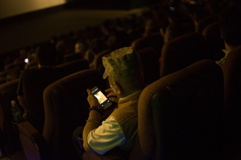 High Angle View Of Man Using Mobile Phone While Sitting On Seat In Theater