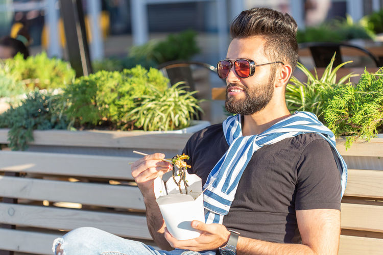 Midsection of man holding ice cream cone outdoors