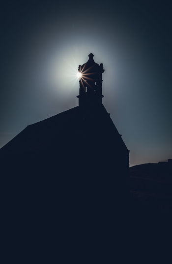 Low angle view of silhouette statue by building against sky