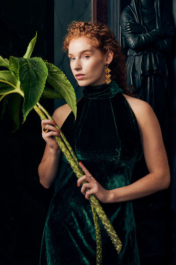 Beautiful young woman holding plant