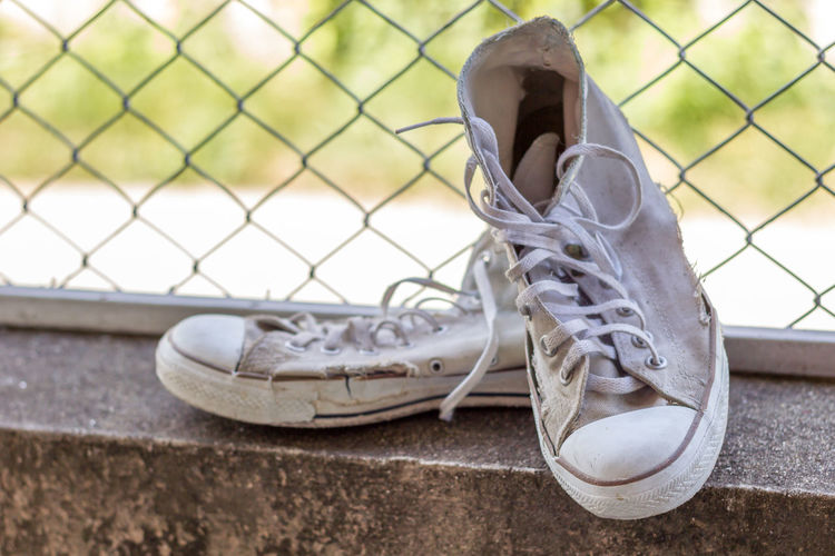 Dirty shoes put on cement back is a mate mesh. Classic Fashion Retro Shoe Active Canvas Shoe Compatibility Day Dirty Extreme Close Up Footwear Grunge Jogging Lace Low Section Old Outdoors Pair Personal Accessory Shoelace Shoes Sneakers Sport Still Life White Color