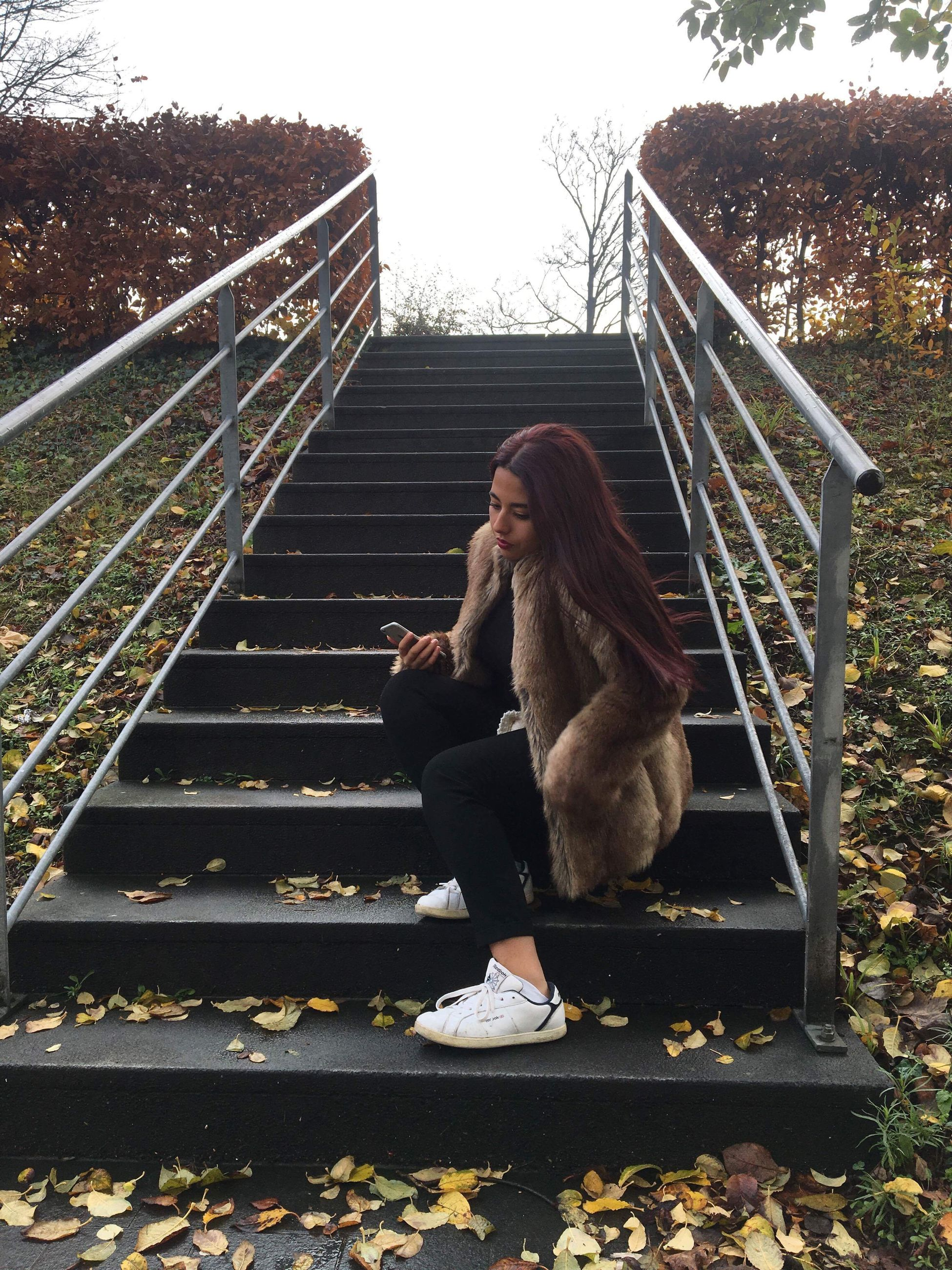 full length, steps, railing, steps and staircases, one person, staircase, real people, young adult, sitting, outdoors, young women, day, nature, people