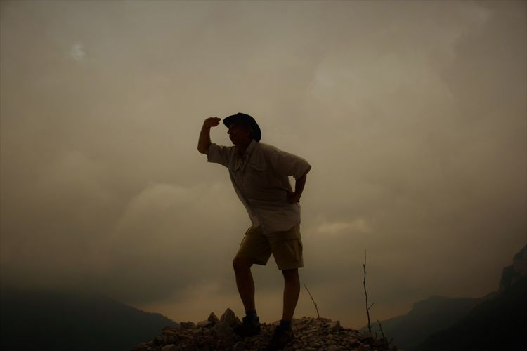 Low Angle View Of Man Standing On Mountain Against Cloudy Sky During Sunset