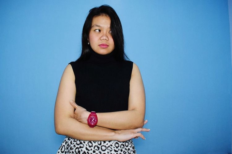 Portrait of a beautiful young woman over blue background
