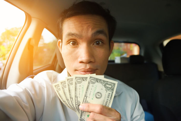Portrait of mid adult man holding paper currencies while sitting in car