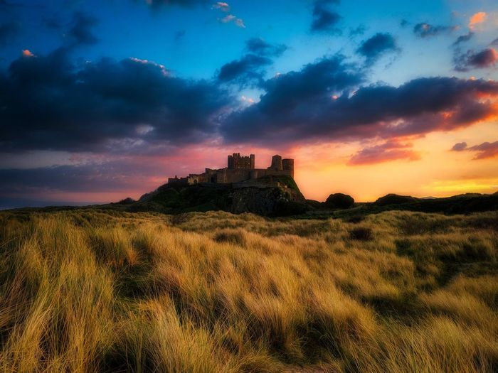 Castle on field against sky during sunset