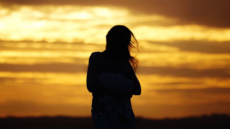 Rear view of silhouette woman standing against orange sky