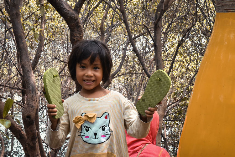 Childhood Child One Person Tree Portrait Front View Looking At Camera Casual Clothing Smiling Plant Leisure Activity Real People Day Happiness Holding Innocence Girls Nature Outdoors