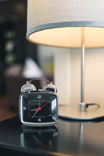 Close-up of alarm clock by illuminated lamp on table