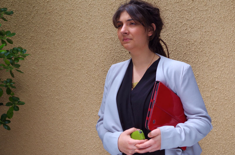Young businesswoman with file and phone standing against wall