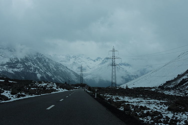 Empty road leading towards snowcapped mountain