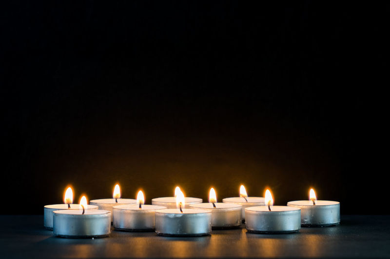 Close-up of candles burning on table against black background