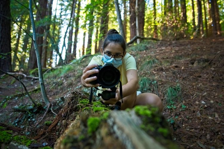 A teenage girl records a video on a fallen tree in the forest