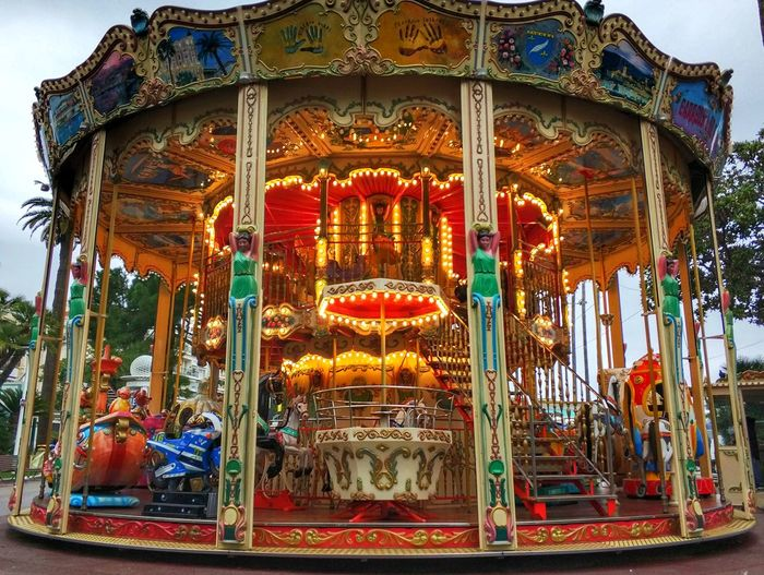 Low angle view of illuminated carousel against sky