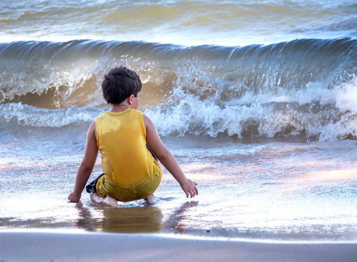 Rear view of boy in sea