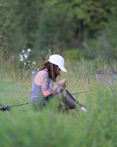 Girls can fish too. tying a line into a fishing pole on the bank of a river.