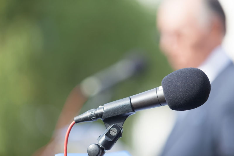 Close-Up Of Microphone With Businessman Standing In Background
