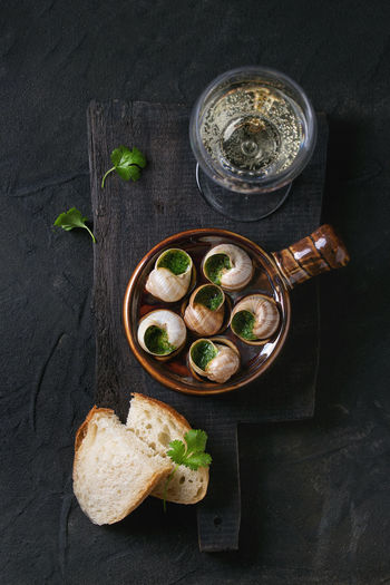 Escargots de Bourgogne - Snails with herbs butter, in traditional ceramic pan with parsley, bread and glass of white wine on wooden chopping board over black textured background. Top view Food And Drink Food Healthy Eating No People Snails Snailshell Escargots Bourgogne Ready-to-eat Butter Herbs Appetizer Flat Lay Top View Copy Space Wine Glass Concrete Balck  Directly Above Wood - Material Board Bread Seafood