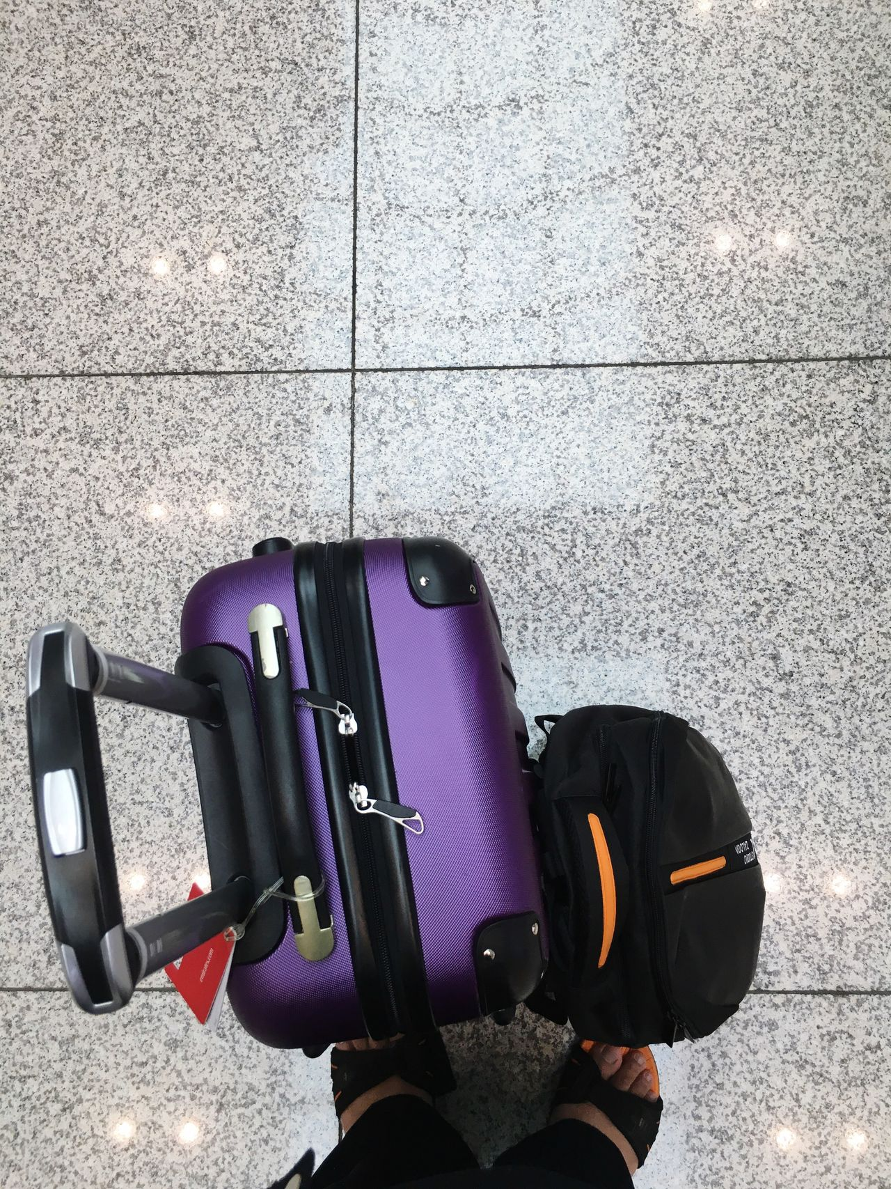 Low section of man standing with suitcase on tiled floor