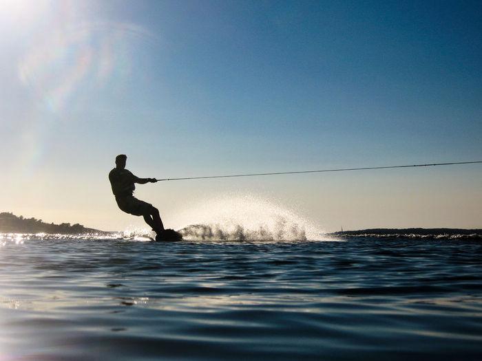 Silhouette man wakeboarding in sea