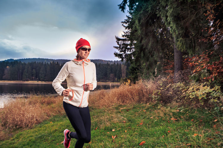 woman running through the forest by the lake Action, Activity, Adult, Autumn, Competition, Female, Fitness. Fit, Forest, Green, Healthy, Hill, Jogging, Lake, Landscape, Lifestyles, Morning, Mountain, Nature, People, Power, Running, Sports, Training, Trees, Water, Woman, Woods Adult Casual Clothing Clothing Day Front View Grass Happiness Land Nature One Person Outdoors Plant Sky Smiling Sport Standing Three Quarter Length Tree Young Adult