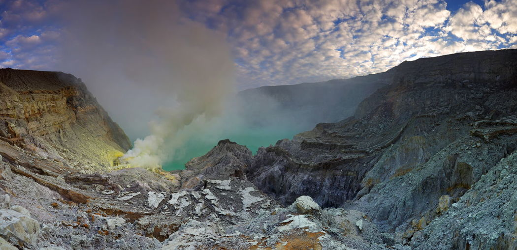 Panorama view of crater with colorful sky at tropical forest with path to the Kawah Ijen volcano, East Java, Indonesia INDONESIA Panorama Beauty In Nature Day Emitting Environment Formation Geology Kawah Ijen Land Landscape Mountain Nature No People Non-urban Scene Outdoors Physical Geography Power In Nature Rock Rock - Object Scenics - Nature Smoke - Physical Structure Solid Volcanic Crater Volcano
