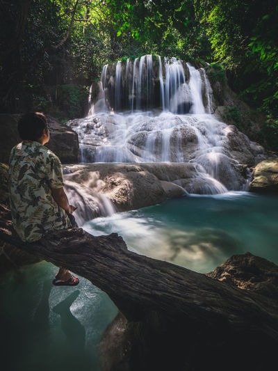 Solo traveler relax and looking at scenic waterfall in forest. erawan fall, kanchanaburi, thailand.
