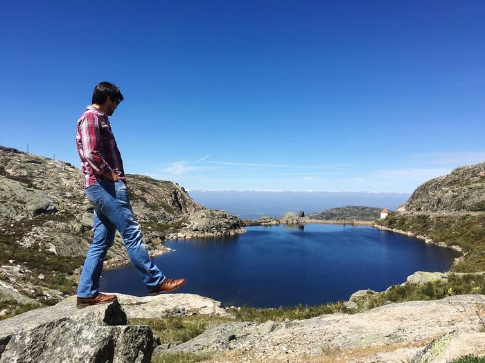 Man standing on rock at torre mountain by lake against sky