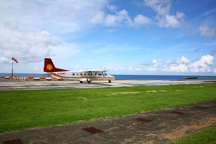 The airplane is on the parking apron beside the sea in Lanyu, Taiwan. ASIA Asian  Grass Orchid Island Taiwan Taiwanese Transportation Travel Airplane Airport Airport Runway Airportphotography Arrival Beside Cloud - Sky Grass No People No People, Runway Runway Airport Sea Sky Transportation