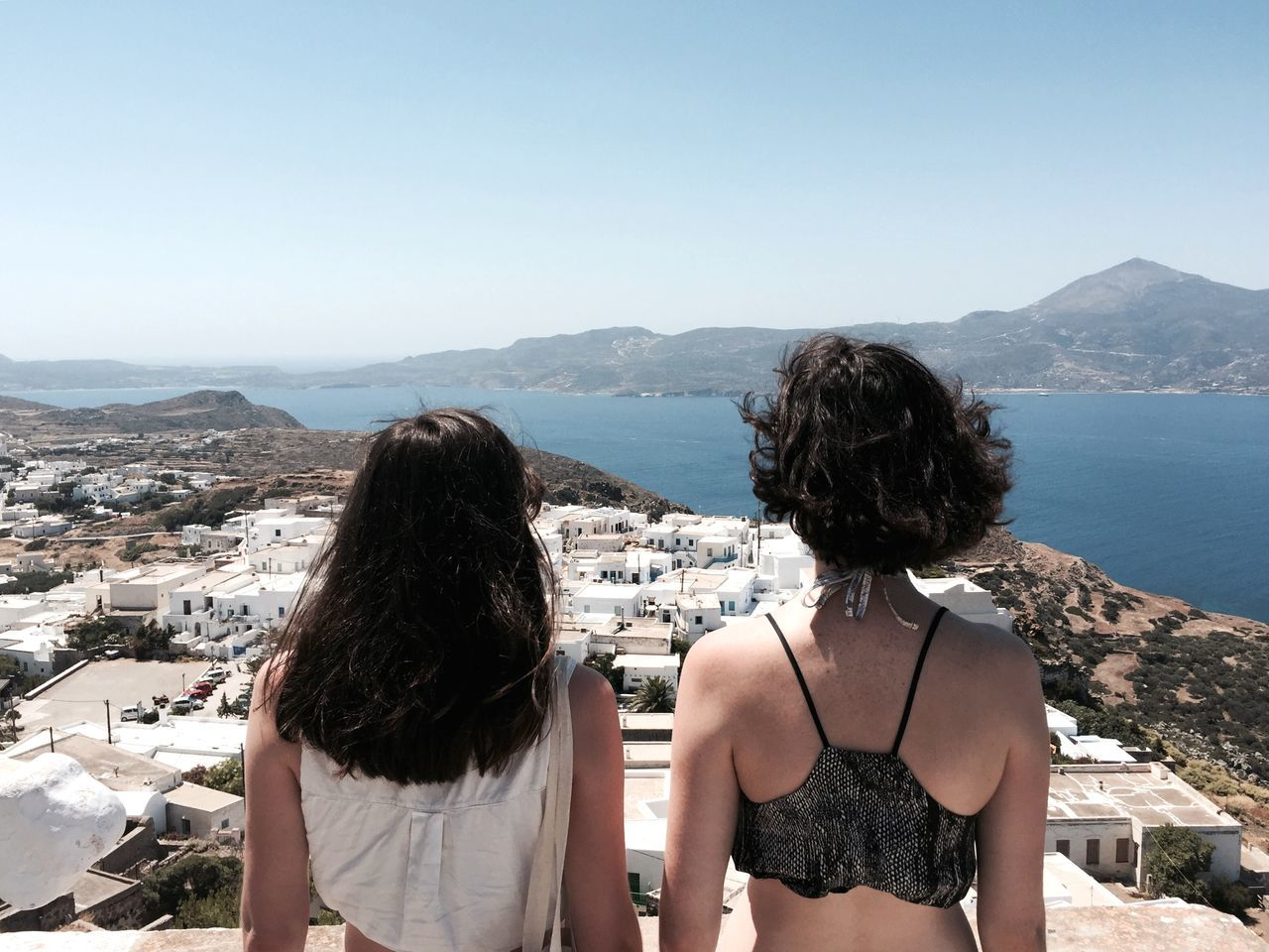 Rear view of women looking at river and mountains against clear sky