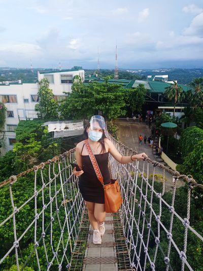 Full length of woman wearing mask standing on footbridge against sky
