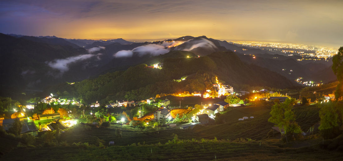High angle view of illuminated mountains against sky at night
