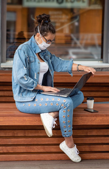 Full length of woman using laptop outdoors