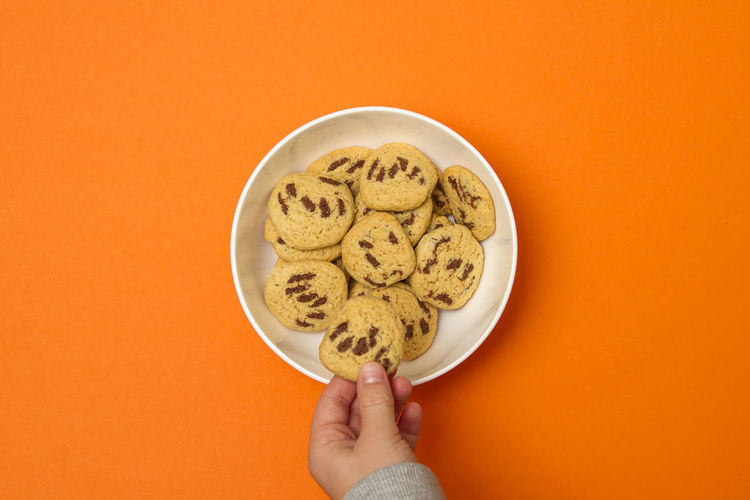 Midsection of person holding bowl against orange background