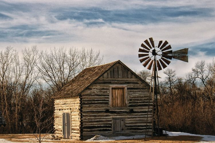 American-Style Windmill Outside Old House Against Sky