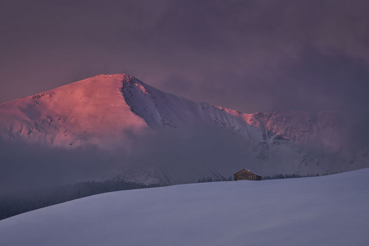 Snow covered mountain against sky during sunset