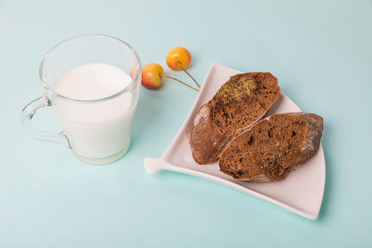 Pieces of rye bread on a white plate, next to a mug with milk on a blue background.
