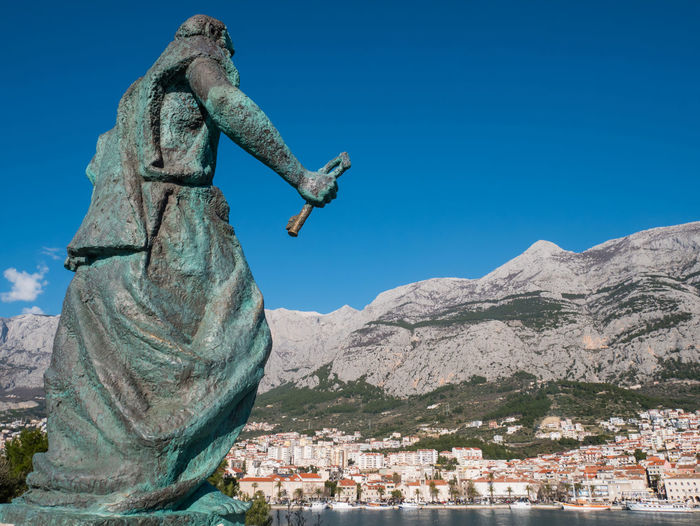 Editorial - Statue of Saint Peter with key in front of city Makarska in Croatia on sunny summer day Saint Peter Monument Sky Architecture Mountain Nature Day Blue Outdoors Old Statue Makarska Makarska Riviera Dalmatia Croatia Europe Adriatic Sea Mediterranean  Heritage Iron Key City Town Famous Architecture Summer Travel Tourism
