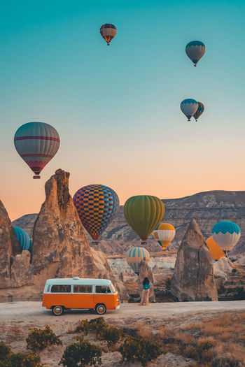 Hot air balloons flying over land against sky during sunset