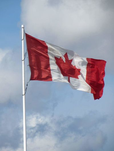 High Section Of Canadian Flag Against Clouds