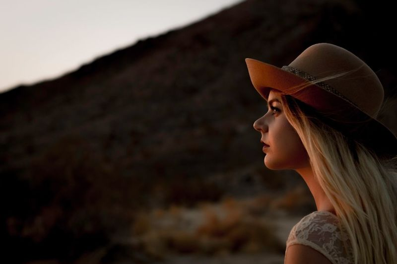 Side view of young woman wearing hat during sunset